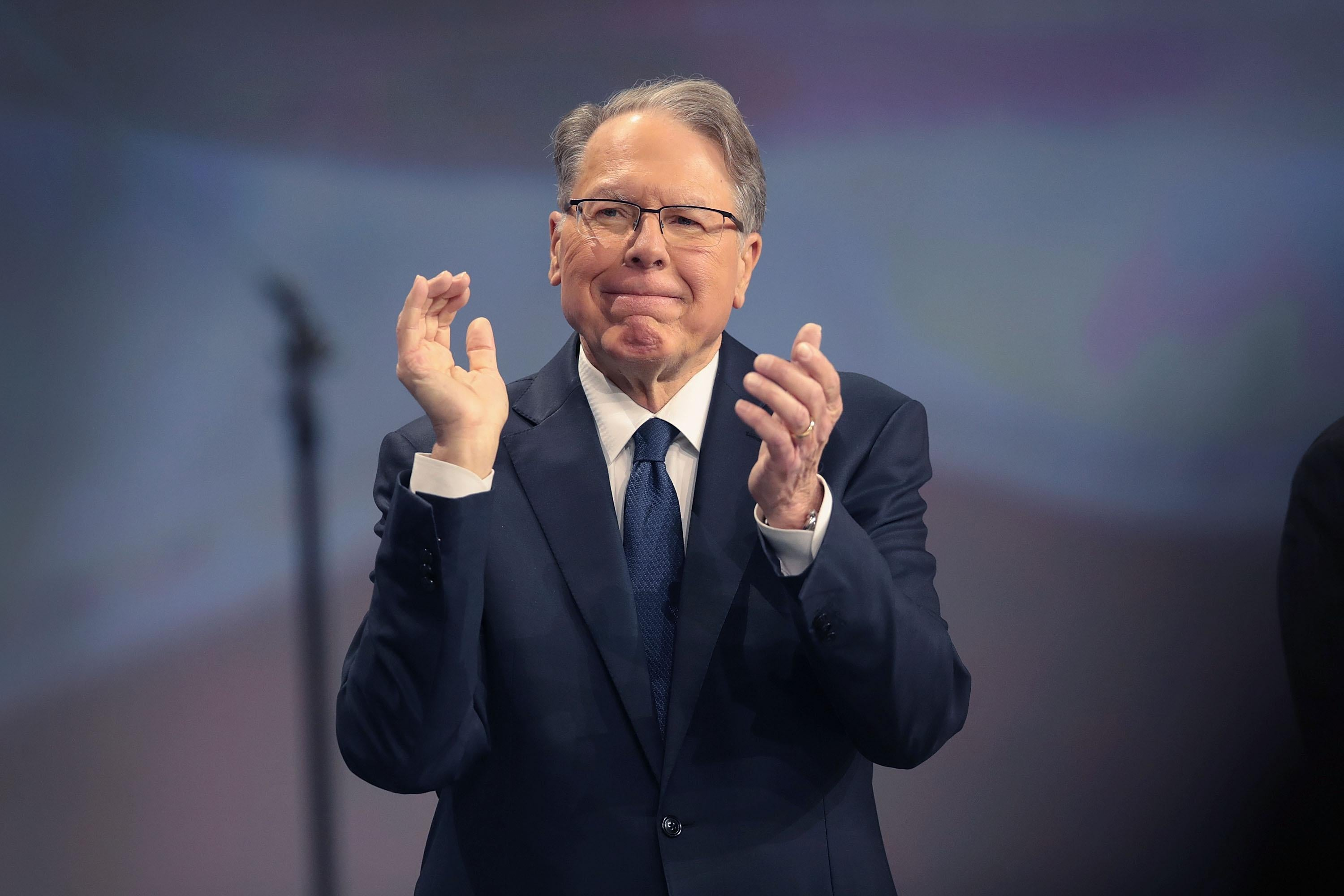 Wayne LaPierre applauds as he stands on stage.