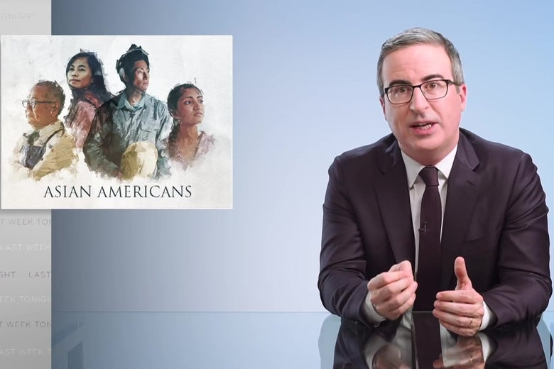 """John Oliver sits at his glass anchor desk in front of a chyron reading """"Asian Americans."""""""