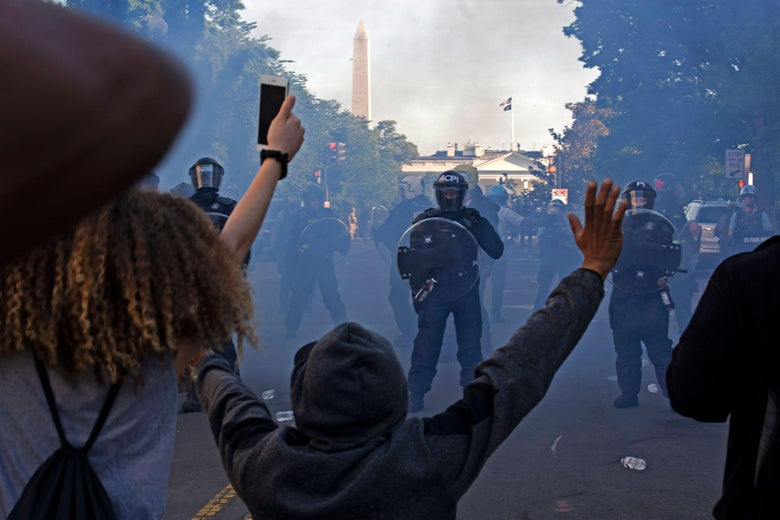 Protesters raise their hands as Secret Service officers can be seen through smoke on a street.