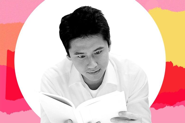 An Asian man reading a book.