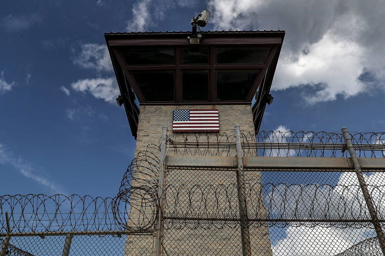 A guard tower marked with an American flag, surrounded by barbed wire