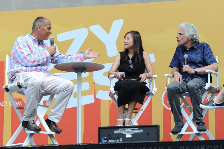 Pinker, sitting in a high folding chair, listens to a moderator's question. There is a woman seated between them onstage and an Ozy Fest backdrop behind them.