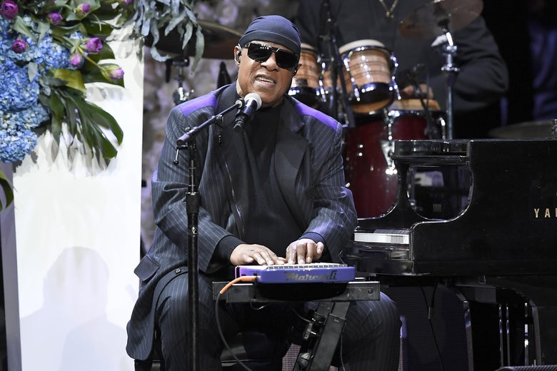 Stevie Wonder playing a synthesizer and singing on a stage decorated with flower arrangements.