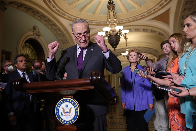 Chuck Schumer makes two fists as he speaks at a podium surrounded by reporters