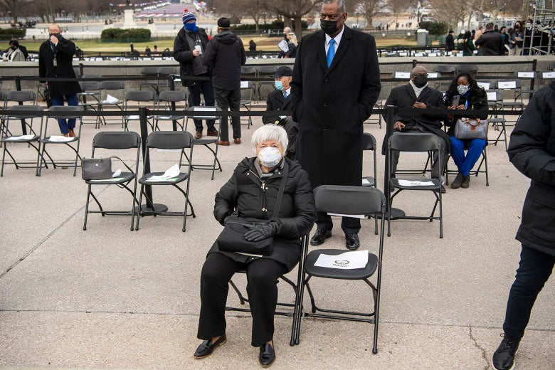 Janet Yellen sits in a folding chair in an all-black outfit with a white mask.