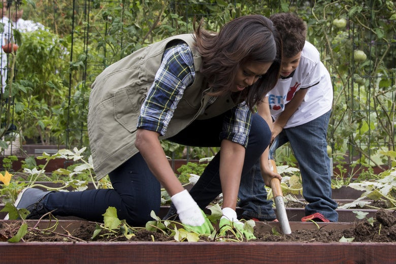 First lady Michelle Obama with a child at a harvesting event at the White House on Oct. 6, 2016.