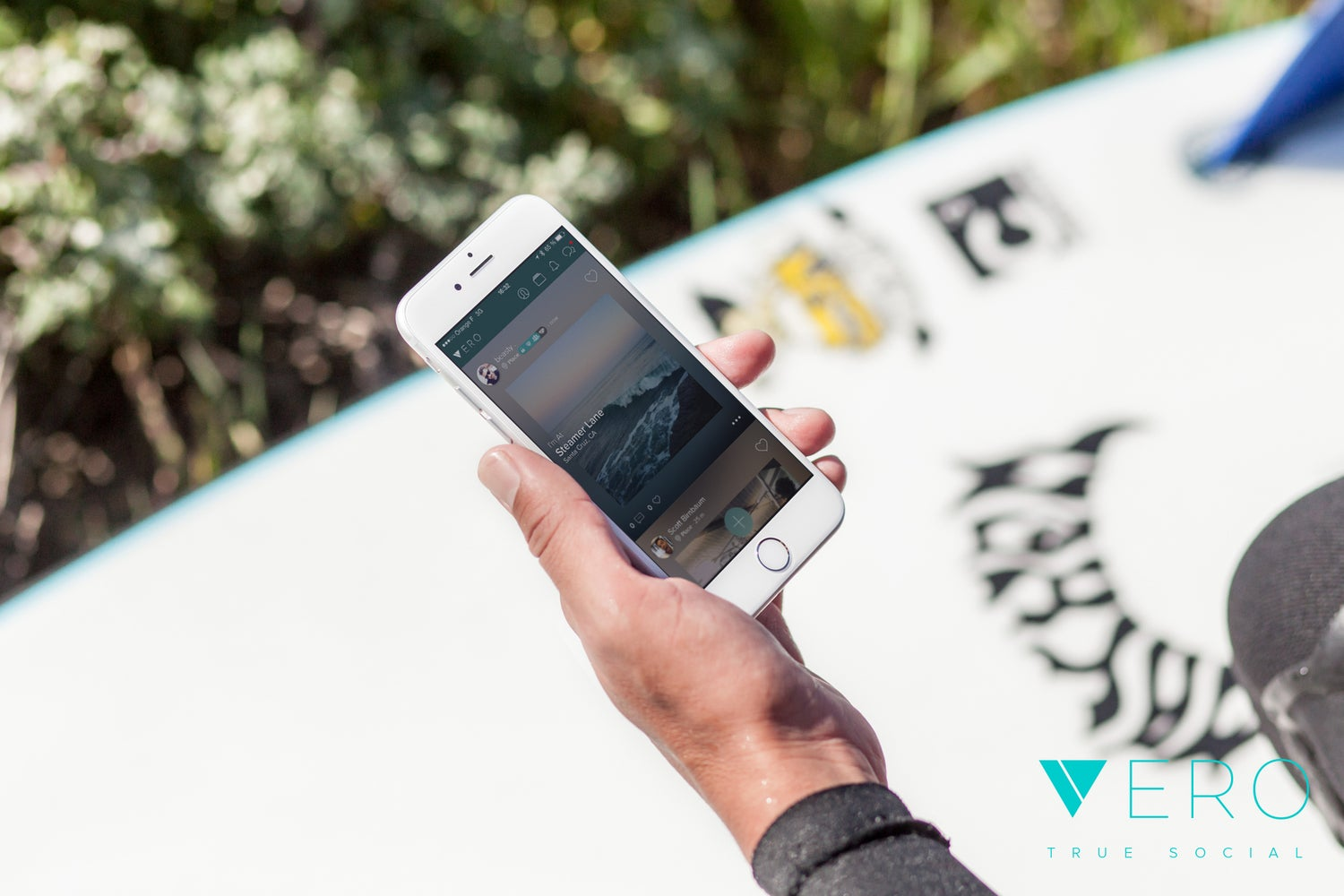 A hand holds a phone with the Vero app.