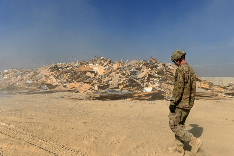 To go with Afghanistan-unrest-US-Bagram,FEATURE by Emmanuel PARISSE In this photograph taken on November 1, 2014, a US soldier walks past a pile of discarded wooden panels and debris - nicknamed 'Mount Trashmore' by the soldiers - during ongoing demolition work in Bagram Air Base, some 50 kms north of Kabul. First they remove the power supply, then they tear out fixtures by hand, before a mechanical digger destroys the roof in a cloud of dust -- the US military is ending its war in Afghanistan and the wrecking crews are busy.  AFP PHOTO/Wakil KOHSAR        (Photo credit should read WAKIL KOHSAR/AFP via Getty Images)