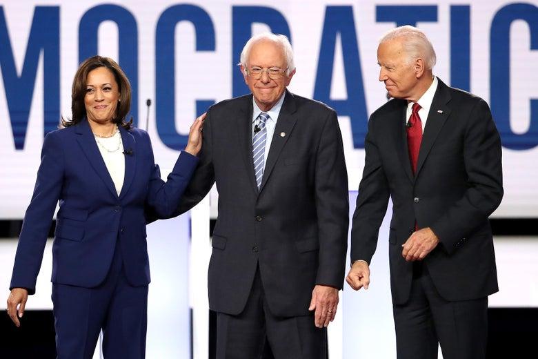 Sen. Kamala Harris puts her hand on Sen. Bernie Sanders shoulder onstage with former Vice President Joe Biden