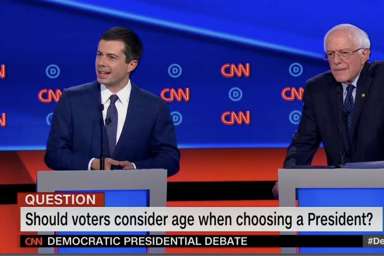 "In this screengrab from CNN, Pete Buttigieg debates while Bernie Sanders makes a concentrating expression. The banner reads: ""Should voters consider age when choosing a President?"""