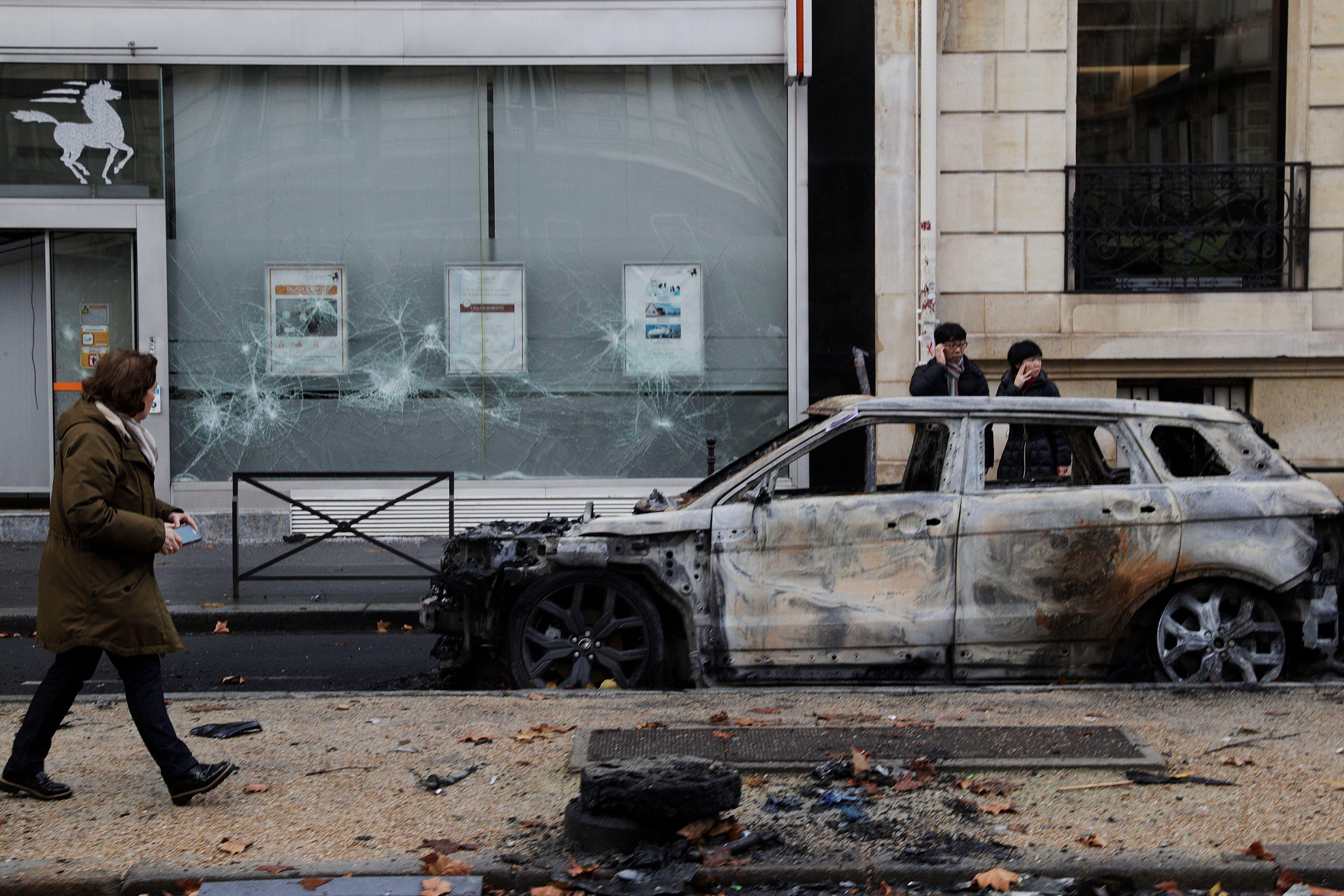 People stand next to a charred car in Paris on December 2, 2018.