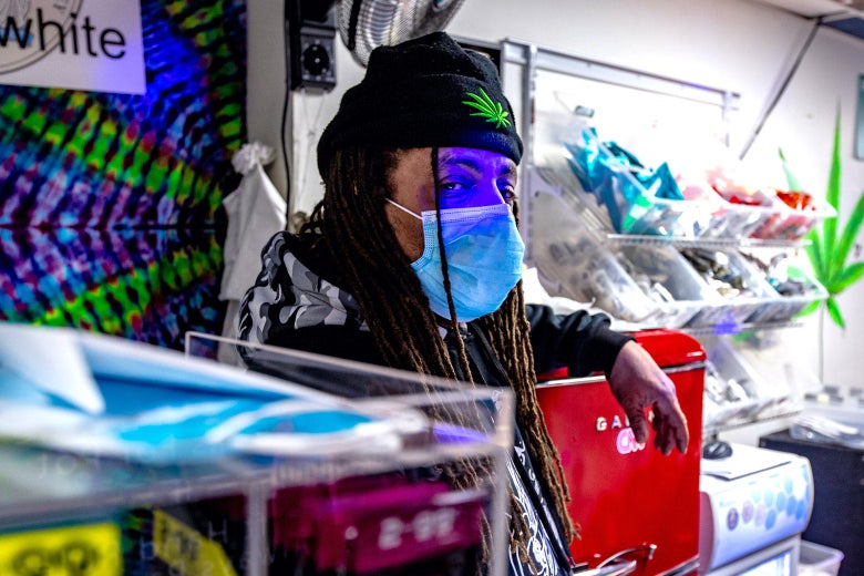 Ed Forchion, masked, in a colorful weed store in Trenton.