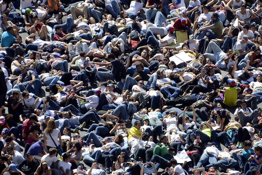 Thousands of anti-government students lie on the ground during a protest in front of the Venezuelan Judiciary building in Caracas.