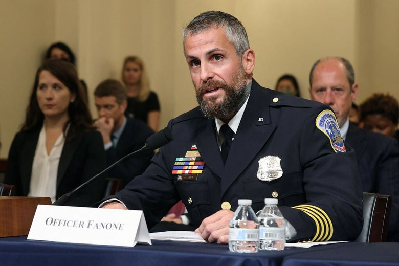 A bearded police officer in dress uniform speaks into a microphone while seated behind a desk in a hearing room.