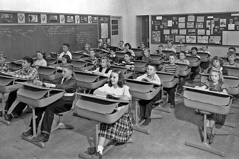 Children sit at desks in a classroom.