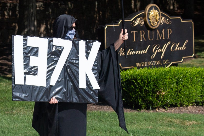 A protester holds a sign with an estimate of the number of dead in the United States from the coronavirus as the motorcade of President Donald Trump arrives at Trump National Golf Club in Sterling, Virginia, on July 12, 2020.