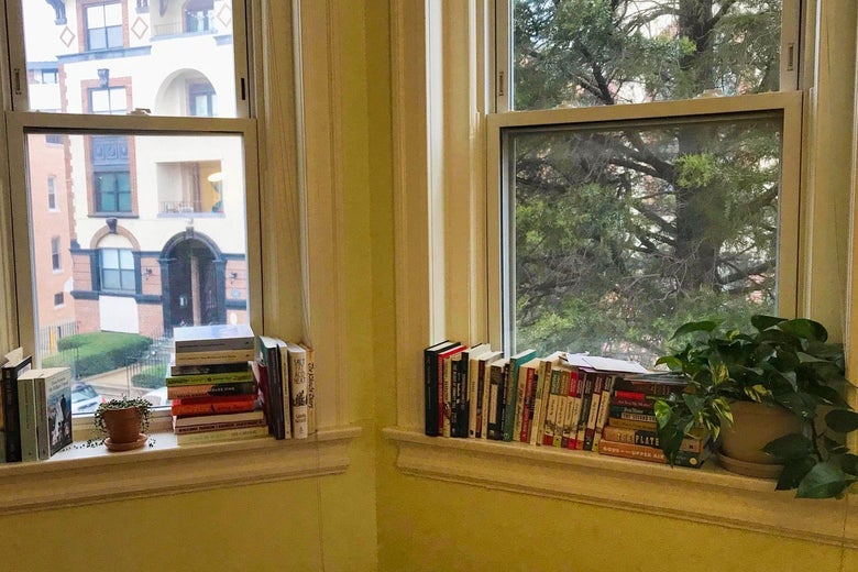 A windowsill covered in books.