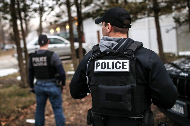 Customs and Border Protection officers stand while wearing police vests on March 29 in Brentwood, New York.