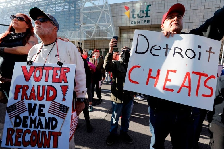 "Older white men hold signs reading ""DETROIT CHEATS"" and ""VOTER FRAUD! WE DEMAND RECOUNT."""