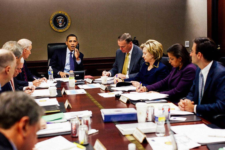 Obama speaks, sitting at the end of a conference table with advisers including Susan Rice and Hillary Clinton