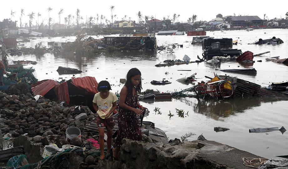 Residents walk near vehicles and debris floating on a river after Super Typhoon Haiyan devastated Tacloban city in central Philippines November 10, 2013.