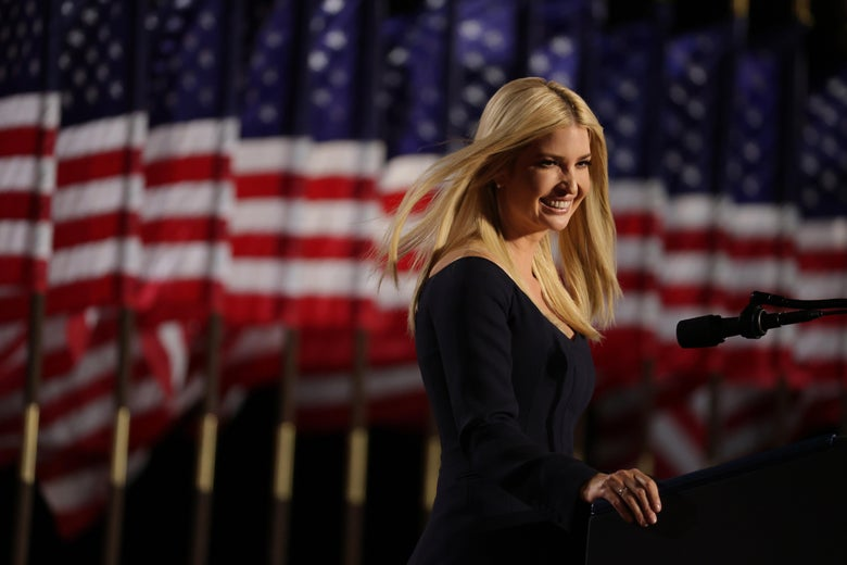 Ivanka Trump standing at a podium, smiling, with American flags in the background