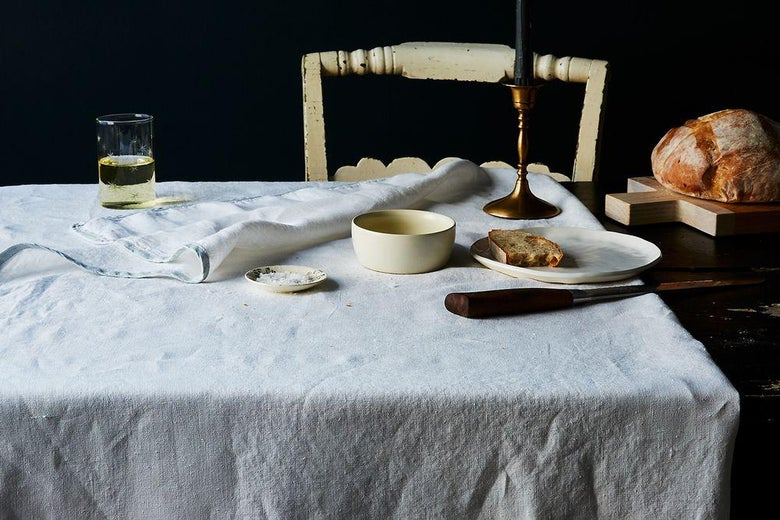 A table with freshly baked bread, sliced, on a rough table cloth, with a candle in an ornate holder.