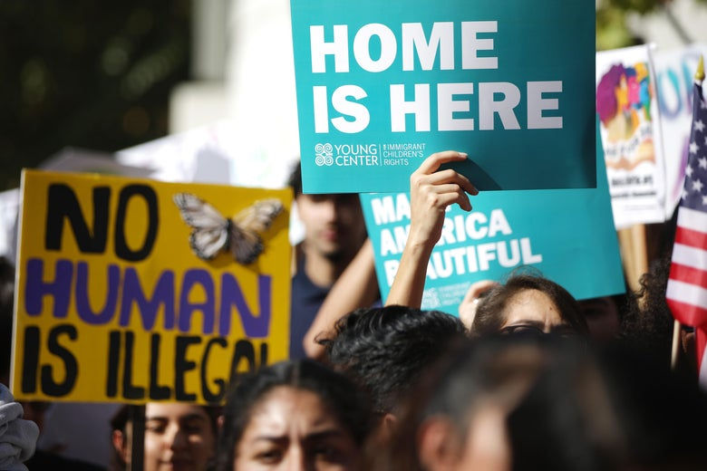 A crowd of people hold up signs saying No human is illegal and home is here.