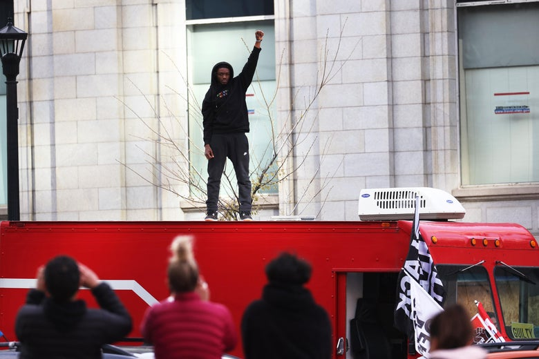 A Black woman stands on top of a truck with her fist up.