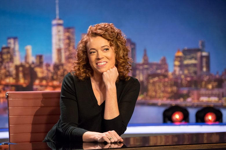 Michelle Wolf sitting behind a desk on the set of her show The Break.