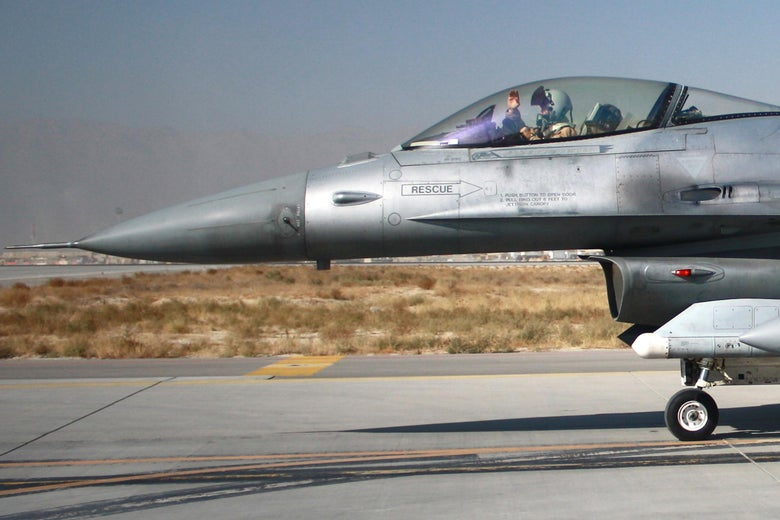 A pilot waves from the cockpit of a fighter jet taxiing on a runway