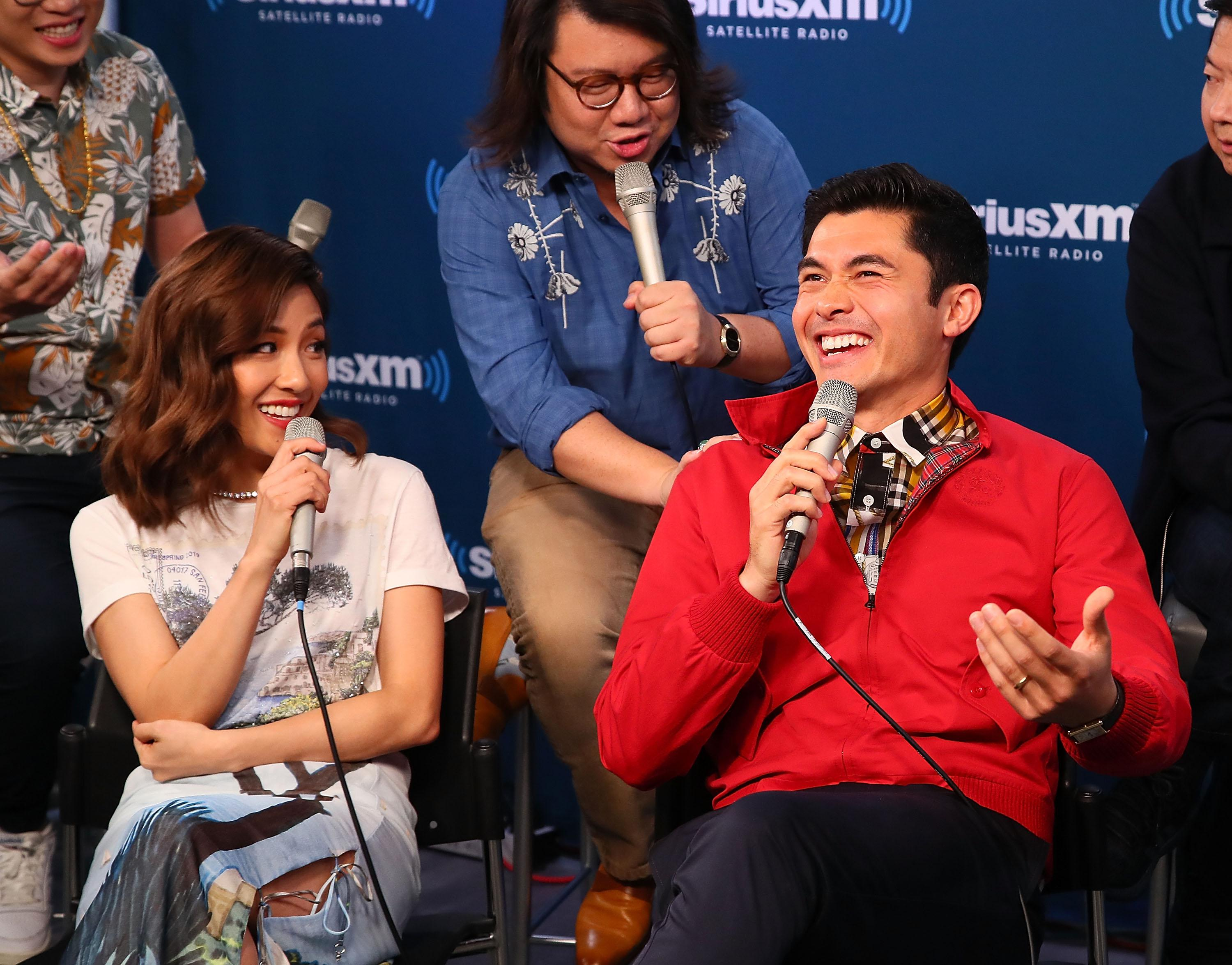 The cast of Crazy Rich Asians talks into microphones for a radio show.