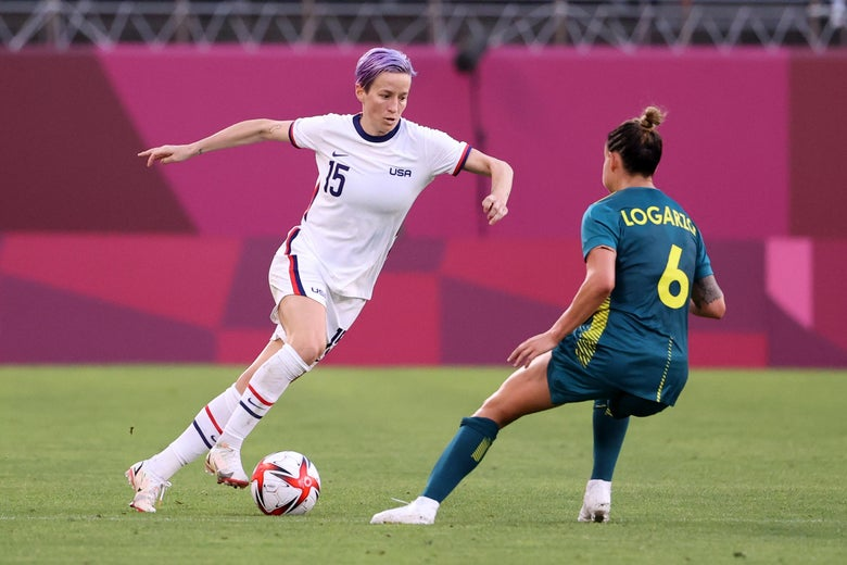 Rapinoe lunging while dribbling the ball, with Logarzo defending tightly.