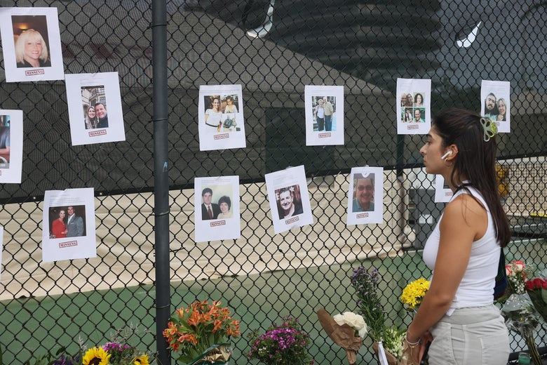Danya Kalla looks at pictures of missing people on June 25, 2021 in Surfside, Florida.