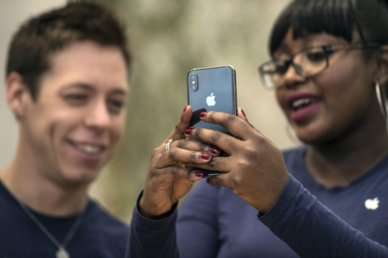 A staff member at an Apple Store in London unlocks an iPhone X with face recognition.