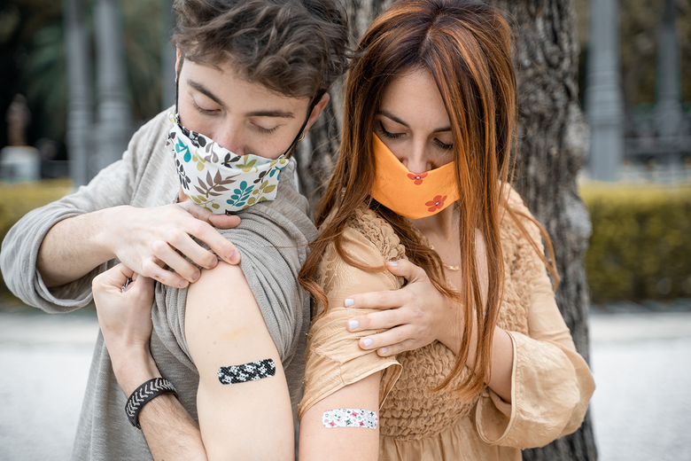 Two young people in masks show off bandages on their upper arms.
