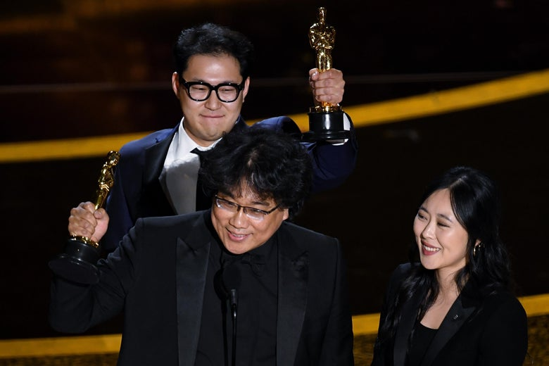 Bong and Han hold their statuettes aloft as Choi stands nearby.