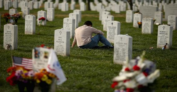 A man pauses between rows of headstones in Section 60, where most casualties of the wars in Afghanistan and Iraq are buried at Arlington National Cemetery.