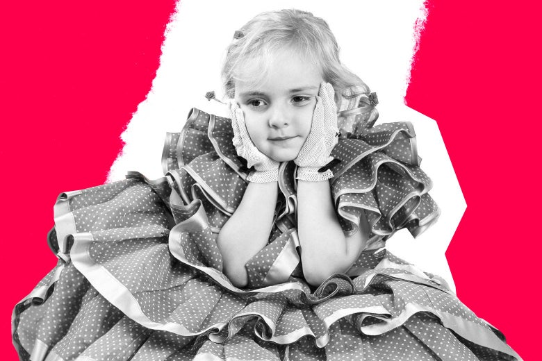 A little girl wearing a frilly dress and gloves poses with her hands on her cheeks.
