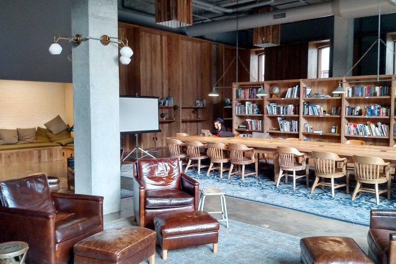 A tastefully decorated library with a long communal table and comfy chairs.