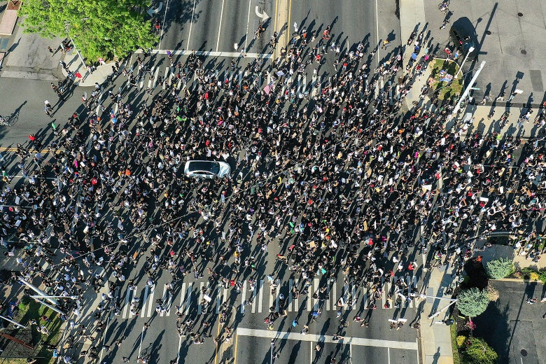 Aerial view of a large crowd of protesters marching through an intersection