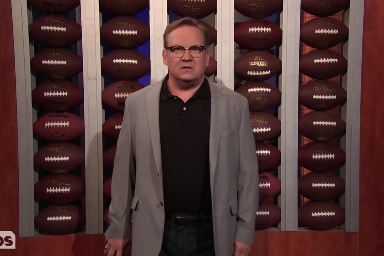 "Andy Richter stands in front of Sports Blast's ""Wall of Basketballs,"" which is a wall of footballs."