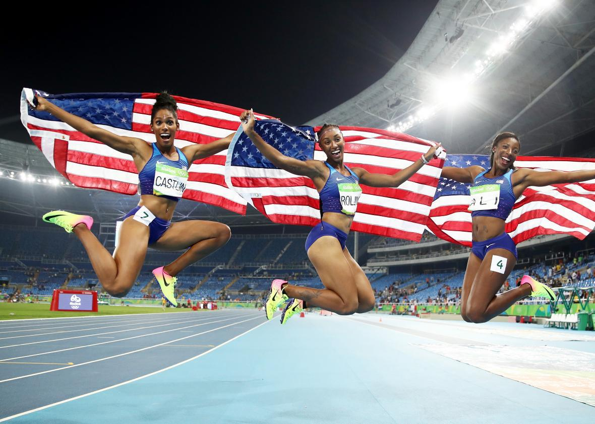 Bronze medalist Kristi Castlin, gold medalist Brianna Rollins, and silver medalist Nia Ali of the United States celebrate with American flags after the women's 100-meter hurdles final on Day 12 of the 2016 Olympic Games at the Olympic Stadium on Wednesday in Rio de Janeiro