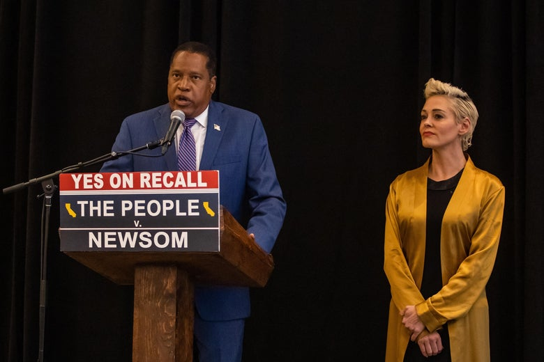 """Larry Elder speaks into a microphone at a podium with a sign that says """"Yes on Recall. The People v. Newsom."""" Rose McGowan stands beside him."""