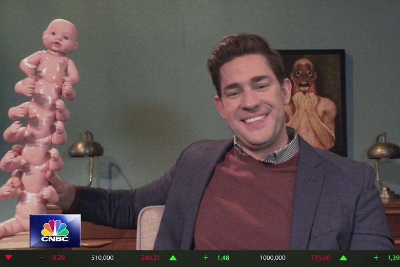 John Krasinski sits at a desk in a still from SNL. To his left is a sculpture made from gluing baby dolls together into a centipede; on the wall behind him is a painting of a man pulling the skin from his own face.