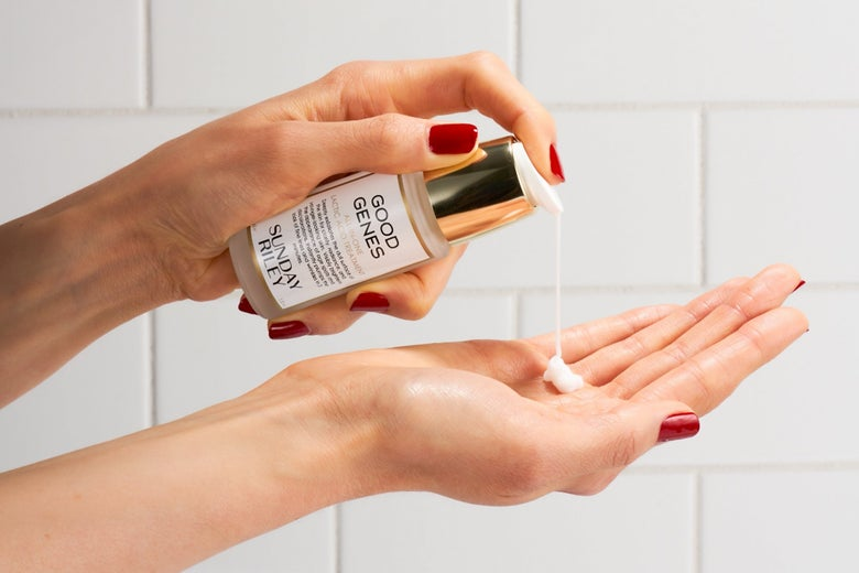 A promotional image for Sunday Riley's Good Genes serum shows a pair of hands using a small bottle.