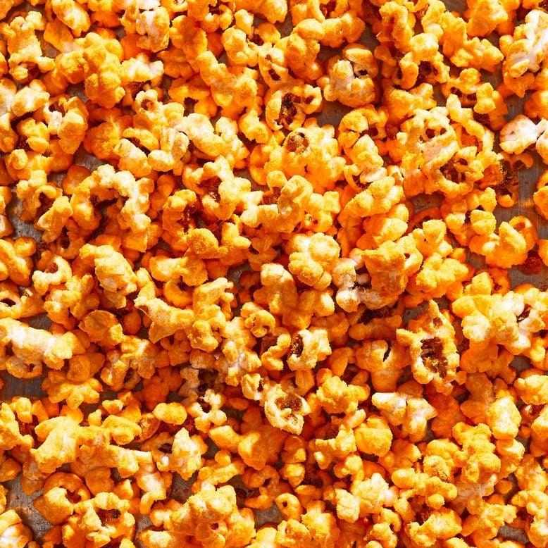Popcorn covered in bright orange cheddar cheese powder