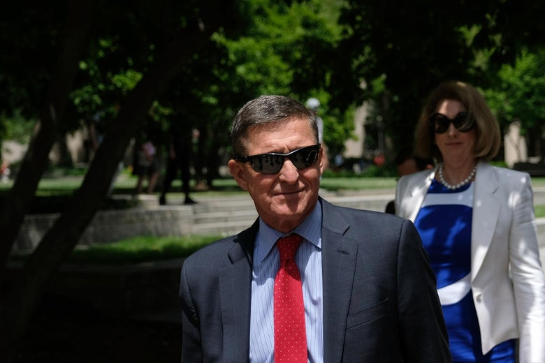Michael Flynn wearing sunglasses and a suit and tie, with a woman in sunglasses walking behind him.