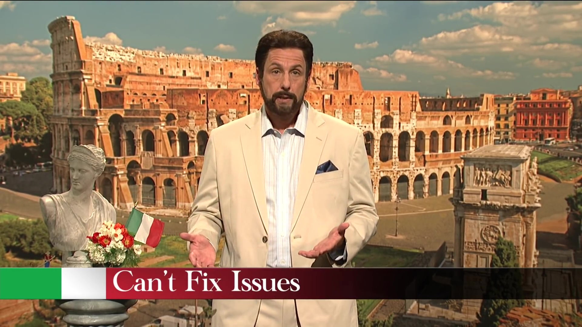 """Adam Sandler stands in front of a photo of the Coliseum, above a chyron reading, """"Can't Fix Issues."""""""