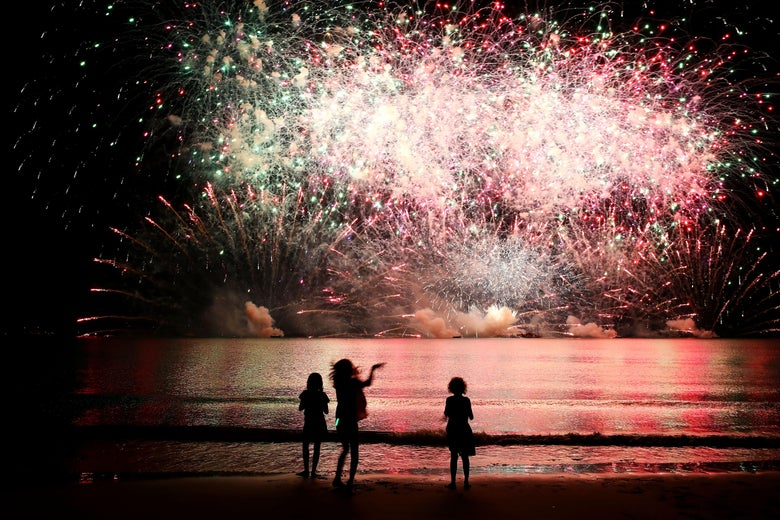 Young girls watch a fireworks display on a beach.